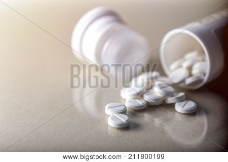 Pills spilling from an open bottle, conceptual image