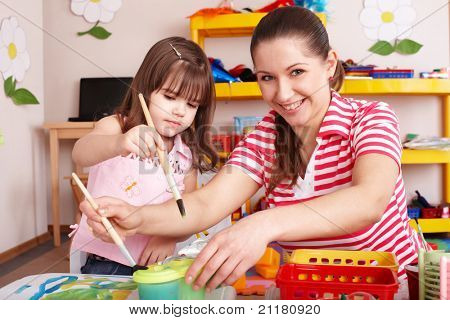 Little girl painting with mother  in preschooler.
