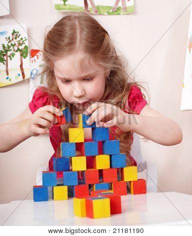 Little girl preschooler play wood block in play room.
