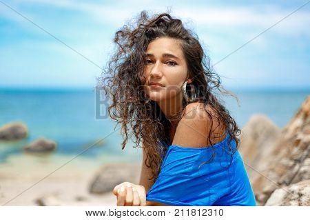 atrractive young woman sitting on the stone at hot sunny day on the beach