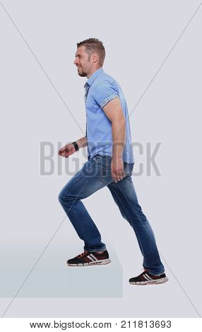 Casual man in blue shirt up the staircase over white background