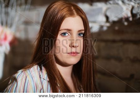 Closeup portrait of attractive young ginger-haired woman looking at camera.