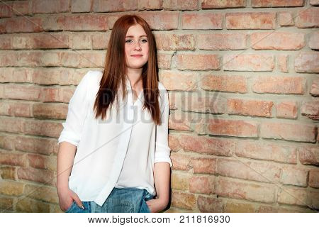 Young ginger girl leaning against brick wall, smiling.
