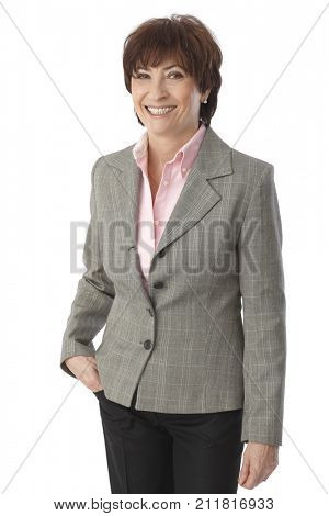Happy senior businesswoman smiling, looking at camera with hands in pocket.