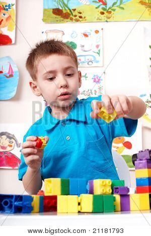 Little boy playing construction set .