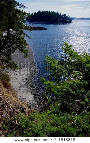 A Sunny View Of Brackman Island With Trees And A Gravel Beach In The Foreground. Taken On A Gorgeous
