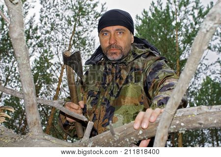 Brutal man chopping wood in the forest