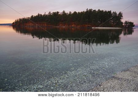 The warm glow of dawn lights Brackman Island off of Portland Island Gulf Islands BC. Brackman Island is reflected in the still waters of the bay. The shell beach in the foreground extends into the clear shallows.