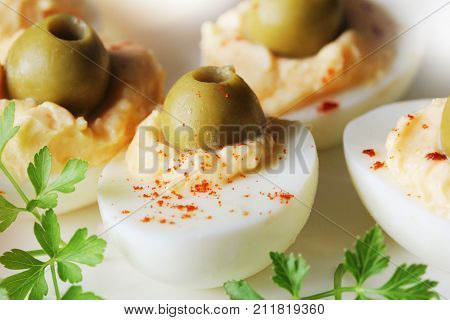 Spicy deviled eggs garnished with green olives .
