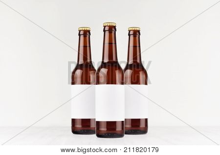 Three brown longneck beer bottles 330ml with blank white label on white wooden board mock up. Template for advertising design branding identity.
