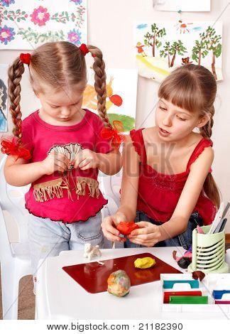 Children playing plasticine.