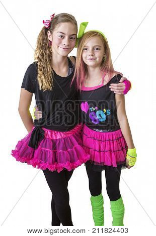 Cute girls dressed in retro 80s decade costumes. Smiling happy girls isolated on a white background