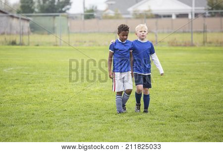 Soccer teammates consoling each other after a tough loss on a soccer field. Concept photo of encouragement from friends after disappointment from a loss