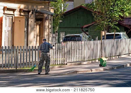 An old man is cleaning up the street in Tallinn Estonia.