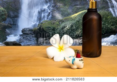 Health care concept incense burner and flower with waterfall in background