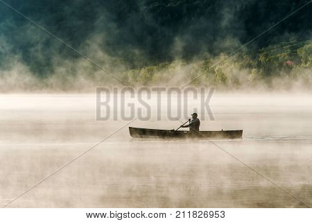 Canada Ontario Lake of two rivers Canoe Canoes on the foggy water sunrise fog golden hour on the water in Algonquin National Park
