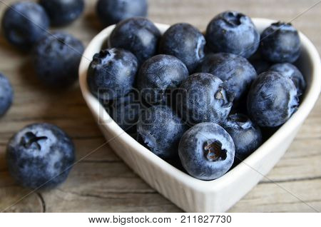 Freshly picked blueberries in a white heart shaped bowl on old wooden background close up.Fresh organic blueberry. Bilberries.Healthy eating,vegan diet or raw food concept.Selective focus.