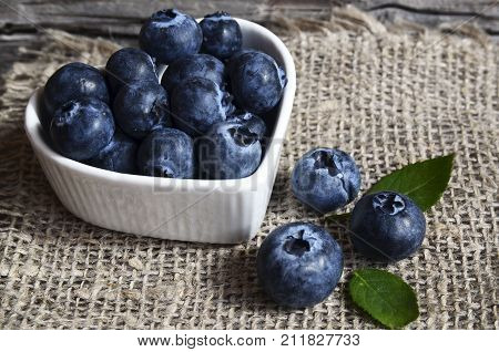 Freshly picked blueberries in a white heart shaped bowl on old wooden background. Fresh organic blueberry.Bilberries.Healthy eating,vegan diet or raw food concept.