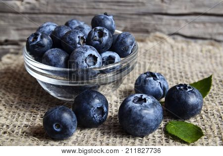 Fresh organic blueberries in a glass bowl on old wooden background.Blueberry. Bilberries.Healthy eating,vegan food,diet and nutrition concept.Selective focus.