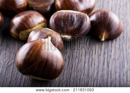Chestnuts over dark wooden table horizontal image