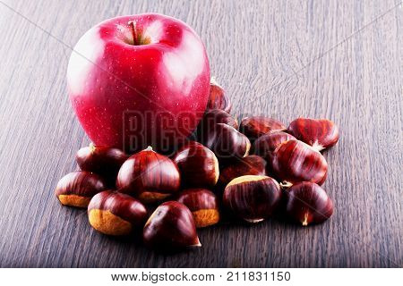 Apple and chestnuts over wooden table horizontal image