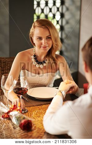 Smiling beautiful woman listening to love confession her boyfriend is telling her