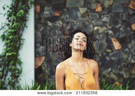 Attractive Latin woman enjoying fresh wind outdoors