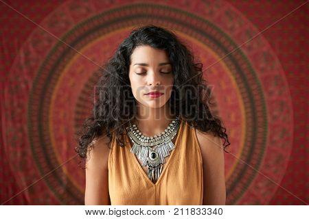 Beautiful Hispanic woman meditating with her eyes closed