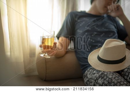 drunken man holding a glass of beer while lying on bed hangover after holiday party alcoholism or alcohol addiction concepts poster