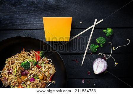 Udon stir fry noodles with chicken and vegetables in wok pan on black wooden background. With a box for noodles. Top view.