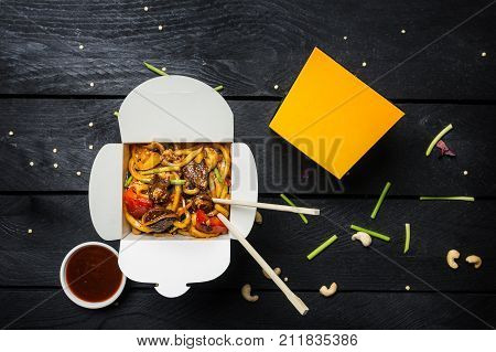 Udon stir fry noodles with meat and vegetables in a box on black background. With chopsticks and sauce. Top view.