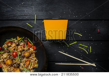 Udon stir fry noodles with seafood and vegetables in wok pan on black wooden background. With a box for noodles. Top view.
