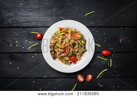 Udon stir fry noodles with seafood and vegetables in a white plate on black wooden background. Top view.