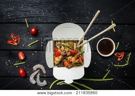Udon stir fry noodles with seafood and vegetables in a box on black wooden background. With chopsticks and sauce. Top view.