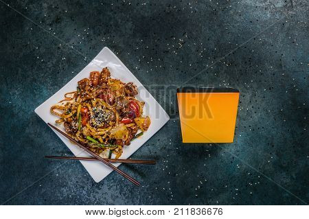 Udon stir fry noodles with meat and vegetables on a square white plate. With chopsticks and box for noodles. Top view.