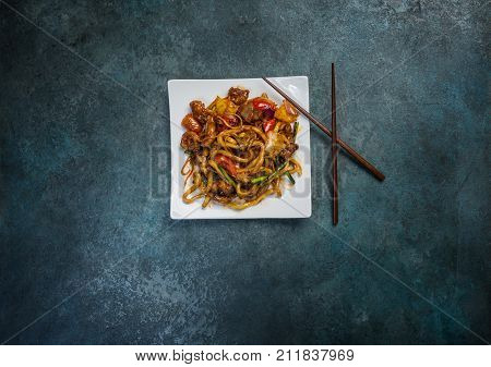 Udon stir fry noodles with meat or duck and vegetables on a square white plate. With chopsticks. Top view.
