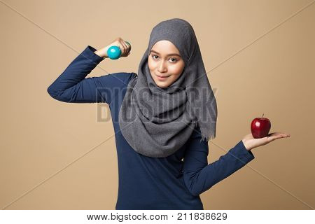a young beautiful hijab woman holding dumbbells and apple on a yellow background.