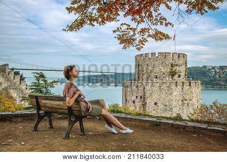 ISTANBUL, TURKEY: Resting girl in Rumeli Hisari fortress and the Fatih Sultan Mehmet Bridge on the Bosphorus on October 7, 2017