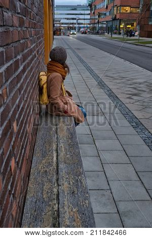 A girl with yellow backpack is waiting for a bus. Bus stop in the city. Brick walls, wooden bench. Safety, comfort. Vertical