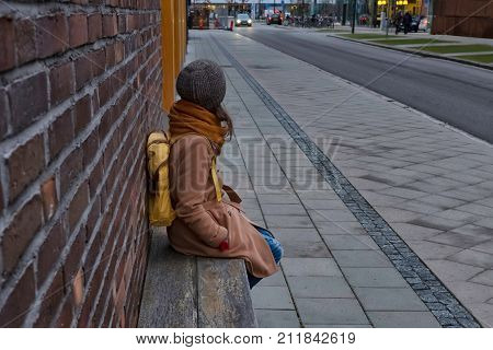A girl with yellow backpack is waiting for a bus. Bus stop in the city. Brick walls, wooden bench. Safety, comfort. Horizontal orientation