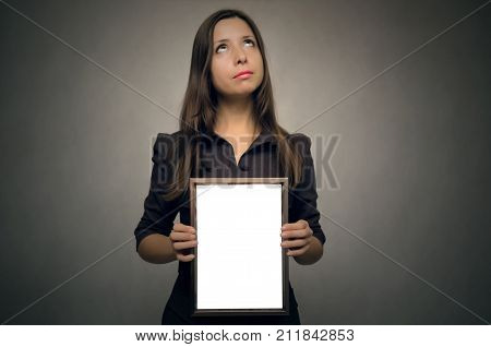 Grateful letter. Gratitude concept. Accolade. Thank letter. Special offer. Young business woman in strict dress holding in hands empty blank photo frame and looking upward. Appreciation document.