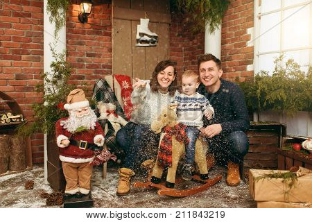 Young Happy Parents With A Cute Little Baby Boy On Rocking Horse, Dressed In Sweaters, Jeans And Boo
