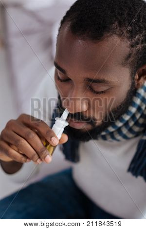 Curing nose. Serious calm responsible man curing his running nose while being at home