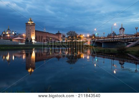 Kolomna Moscow Region. Beautiful View: Assumption Brusensky Female Monastery Church Of Michael Archangel And Marinkin Tower Of Kremlin With Illumination By River On Blue Hour At Autumn Evening.