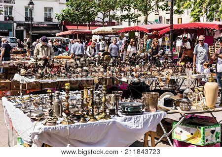 Paris France - Jule 09 2017: People choosing rare and used books wooden masks and figures of African culture at the historic flea Aligre Market (Marche d'Aligre) in the Bastille district.