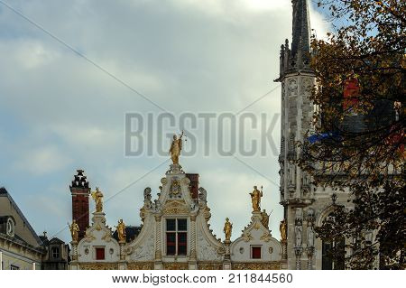 Satues on the roof of a medieval building in the center of Bruges.