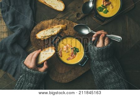 Woman in warm grey sweater eating corn creamy chowder soup with prawns served in individual pots, top view. Woman' s hand keeping spoon and bread slice. Flat-lay of rustic dinner table. Slow food, winter warming food concept