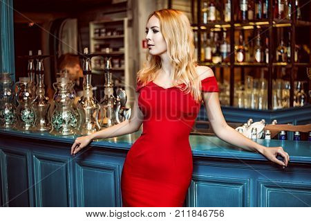 Gorgeous blond woman in fashion red dress staying at the Hookah bar in the club cafe or restaurant