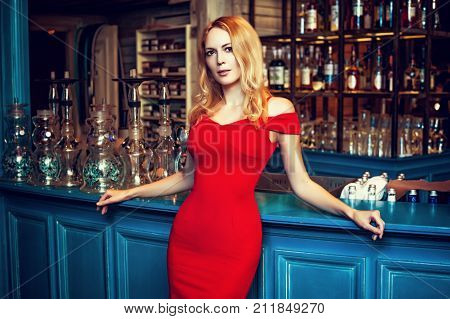 Gorgeous blond girl in fashion red dress staying at the Hookah bar in the club cafe or restaurant