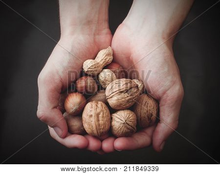 Various unpeeled nuts in hands on dark background